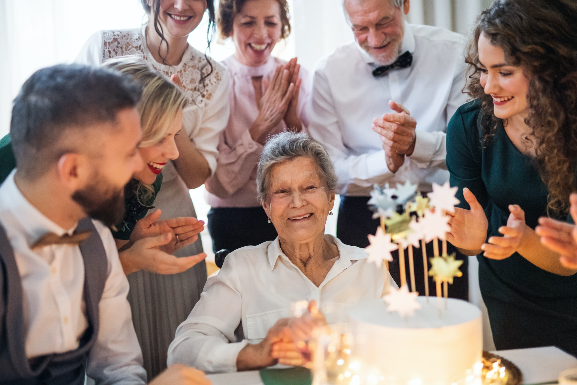An elderly woman with multigeneration family celebrating birthday on indoor party.