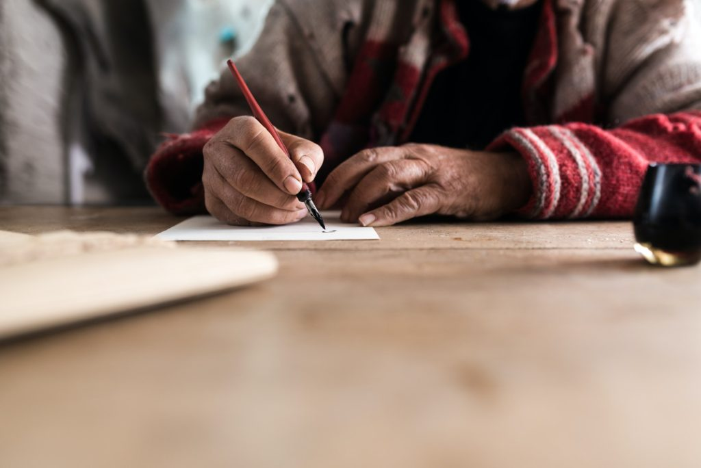 Old man with dirty hands writing a letter using a nib pen and in